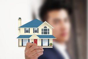 Mężczyzna z modelem domu w ręku