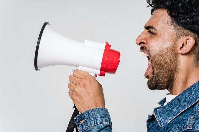 Człowiek krzyczący do megafonu